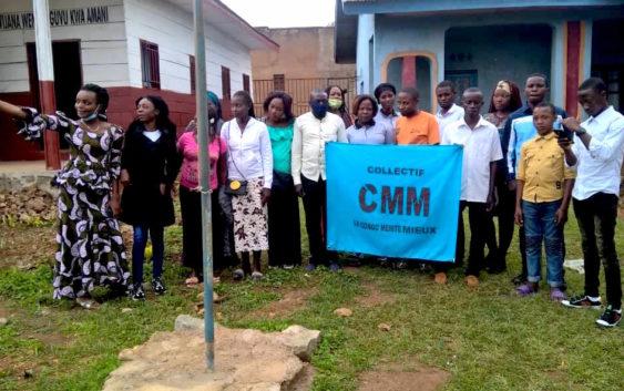 Les membres du Collectif CMM tenant une banderole